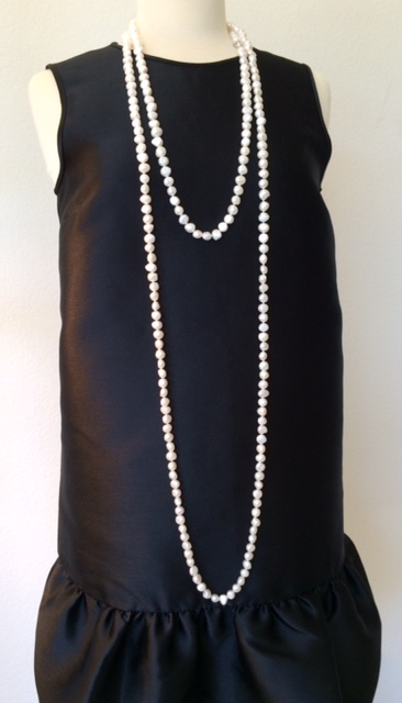 Single strand pearl draped twice